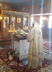 Bishop praying before the icons of Christ and St Nicholas